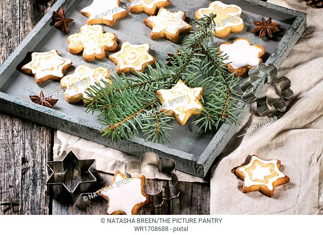 Assorted Christmas cookies on wooden tray, served with Christmas tree branch over old table