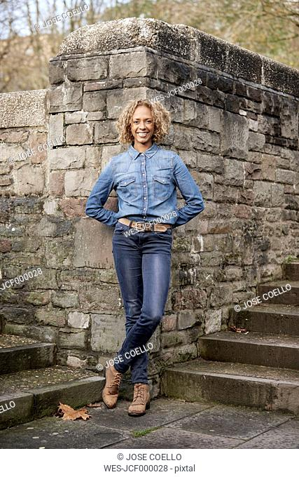 Portrait of smiling woman wearing denim shirt and jeans