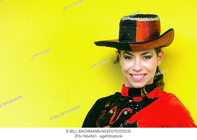 Trinidad Cuba dancer in costume and hat against yellow wall and smile