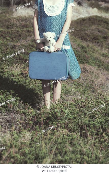 a young girl with a suitcase and a teddy bear