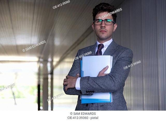 Portrait serious businessman holding paperwork in office corridor