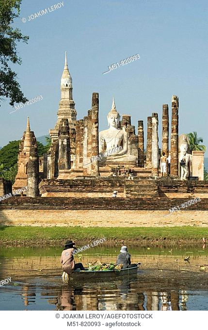 Local people are cleaning up the pond that faces the Wat Mahathat temple in Sukhothai UNESCO site