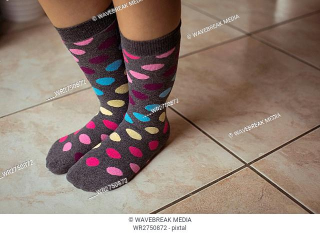 Womans feet wearing multicolored polka dots socks