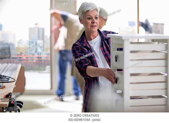 Senior female carpenter checking drawers in furniture making workshop