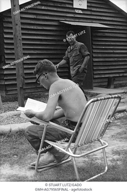 A shirtless United States Army serviceman reading a book while sitting on a lawn chair, another soldier walks past him in the background of the military base