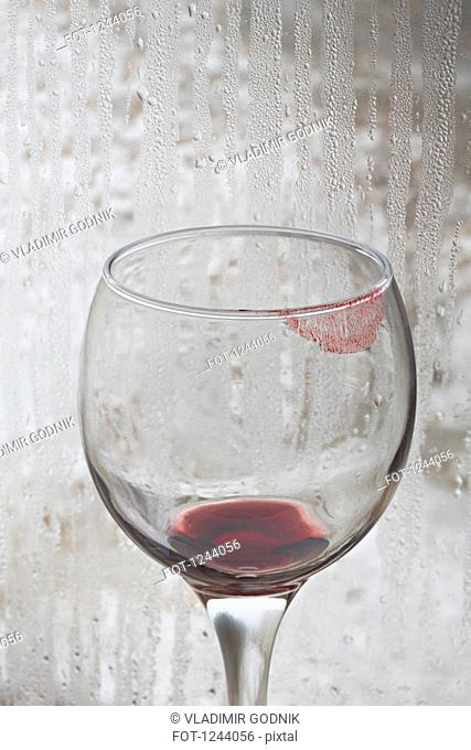 Lipstick on a glass of red wine with rain covered window in the background