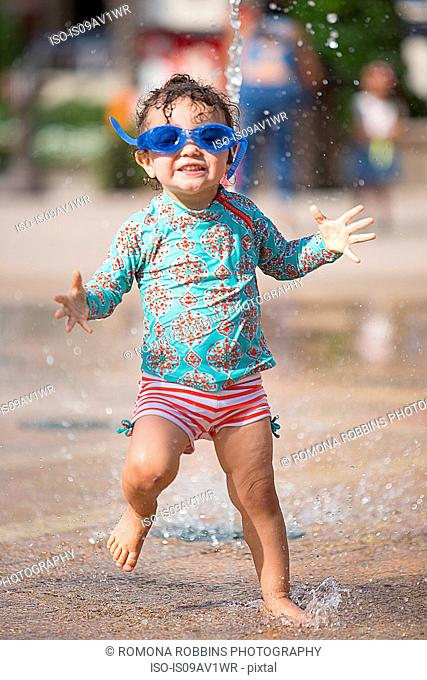 Girl wearing swimming goggles playing in water fountain, looking at camera smiling