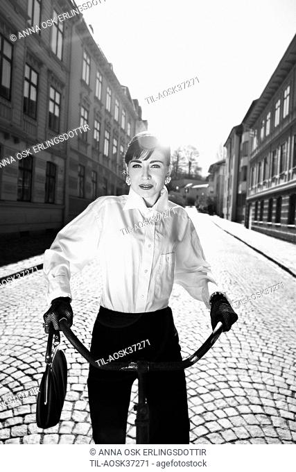 Young adult female wearing white blouse and black trousers dressed elegantly riding a bicycle outdoors in sunlight