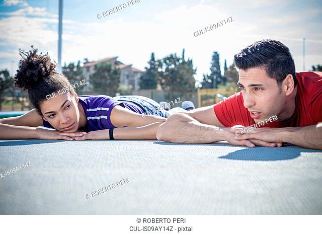 Young man and woman training, taking a break on asphalt