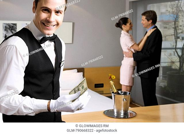 Portrait of a waiter holding US paper currency and smiling