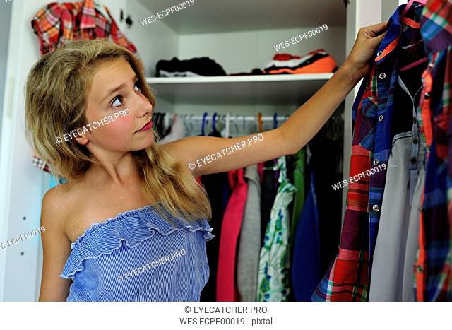 Girl choosing clothes from wardrobe