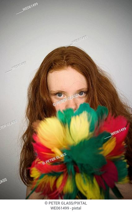 Long red-hair teen girl holding a feather duster