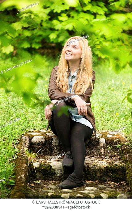 Nature scene with one young attractive blonde woman sitting in a park looking up