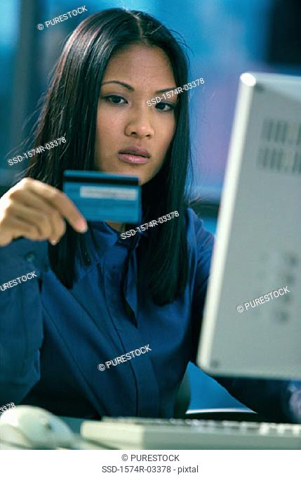 Young woman sitting in front of a computer holding a credit card