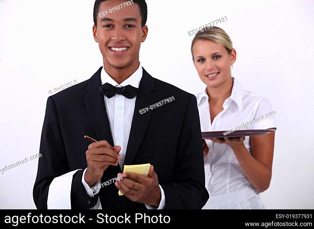 a young latino well dressed waiter writing order and a young blonde waitress hol