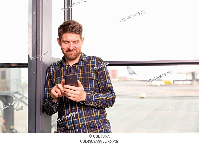 Waist up front view of mid adult man standing in front of airport window using smartphone