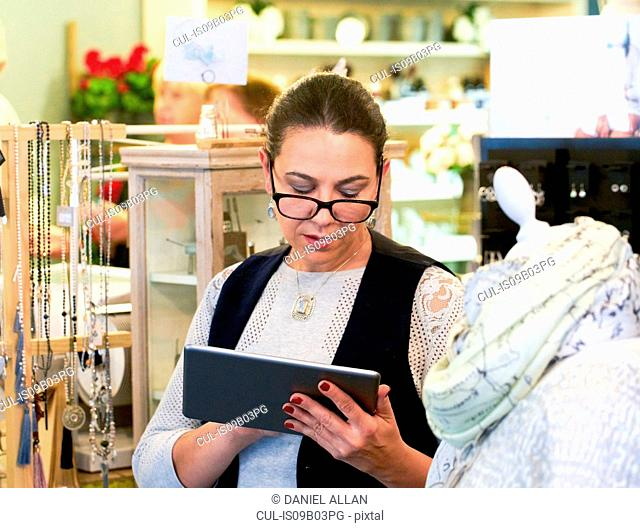Female sales assistant stocktaking using digital tablet in gift shop
