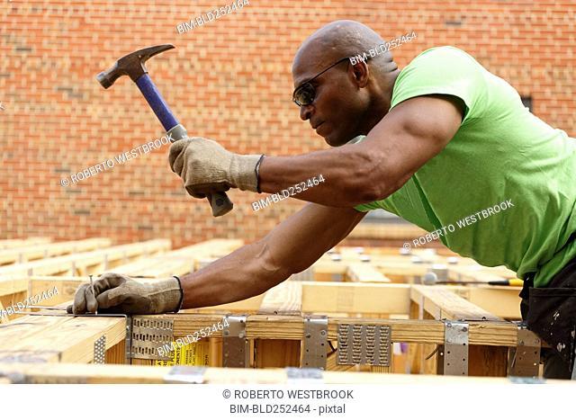 Black man hammering nail at construction site
