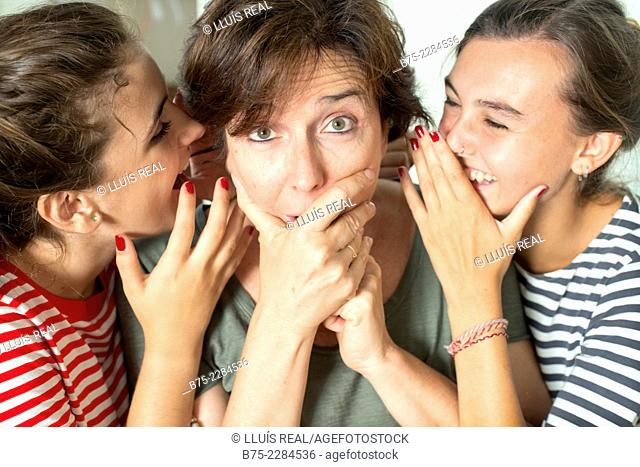 Two young girls with her mother whispering and sharing a secret with surprise