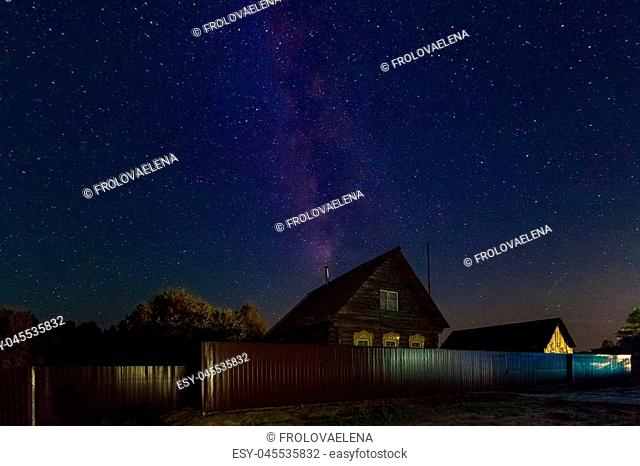 The Milky Way. A beautiful August summer night sky with stars on the background of a village house. Starfall, the falling Perseids