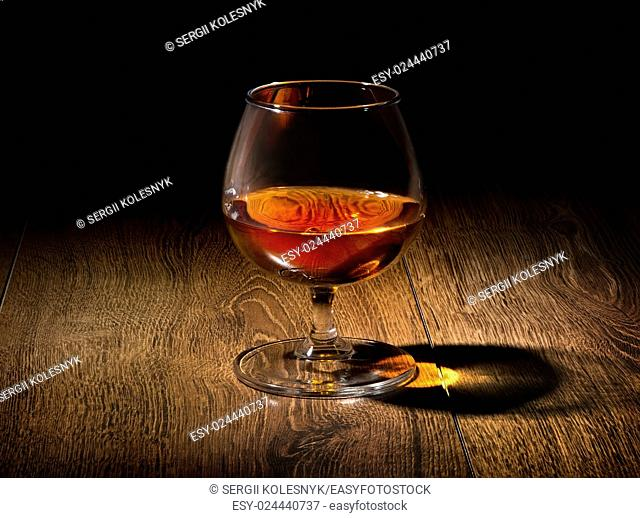 Glass of golden cognac on a wooden table