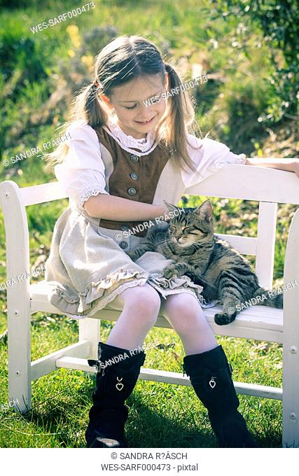 Portait of little girl sitting on wooden bench with cat