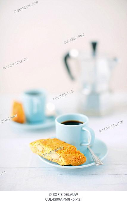 Still life of black coffee and almond cantucci biscuits