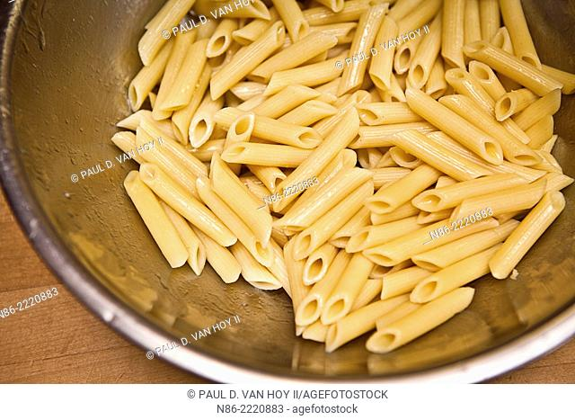 penne pasta in mixing bowl