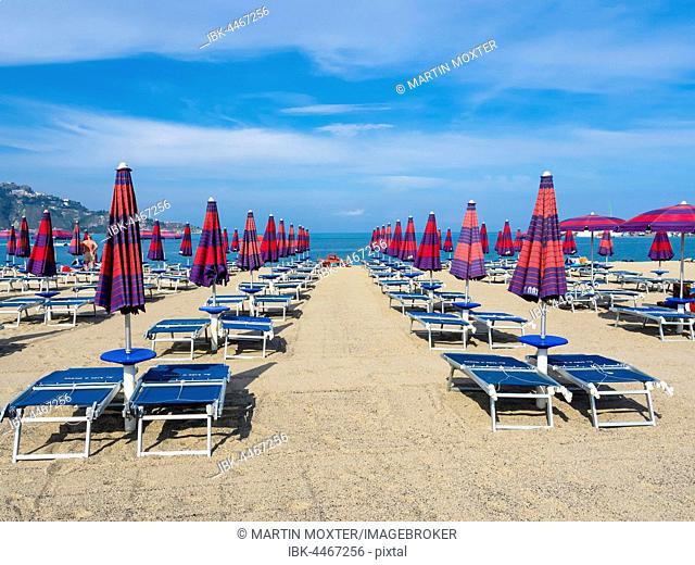 Preseason, closed umbrellas on beach, Giardini, Naxos, Taormina, Sicily, Italy
