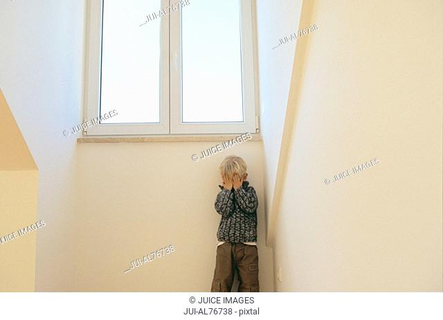 View of a little boy playing hide-and-seek