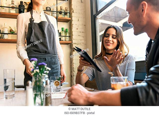 Young woman paying bill at cocktail bar table