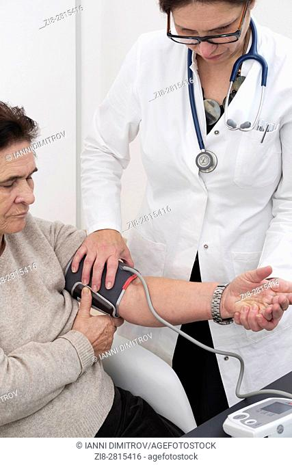 Doctor checks blood pressure of senior female patient