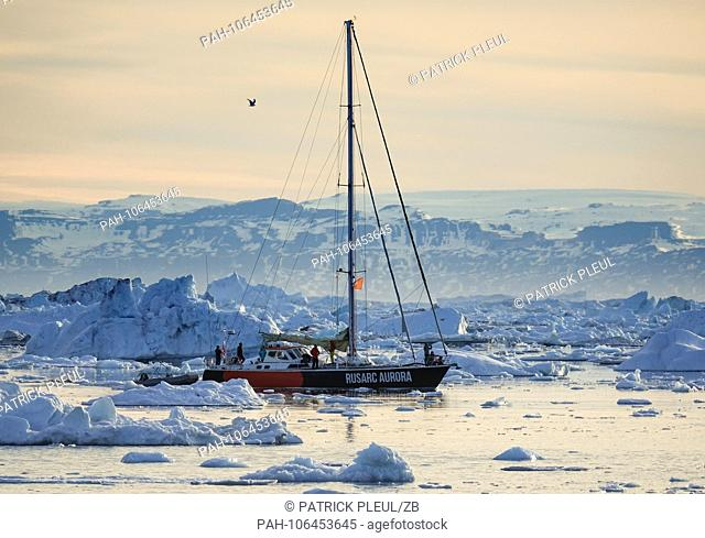 27.06.2018, Gronland, Denmark: A sailing ship cruises late evening between icebergs over the water in front of the coastal town of Ilulissat in western...