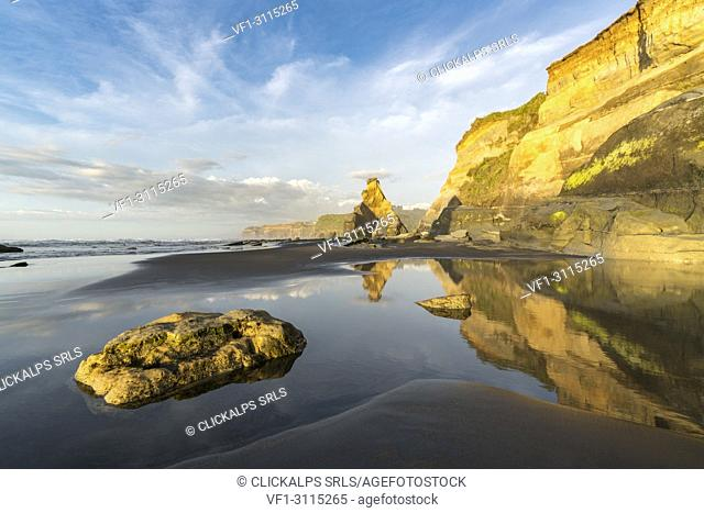 Rock formations and cliff reflect with low tide. Tongaporutu, New Plymouth district. Taranaki region, North Island, New Zealand