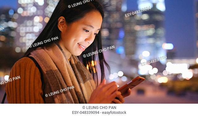 Woman use of smart phone in the city at night time