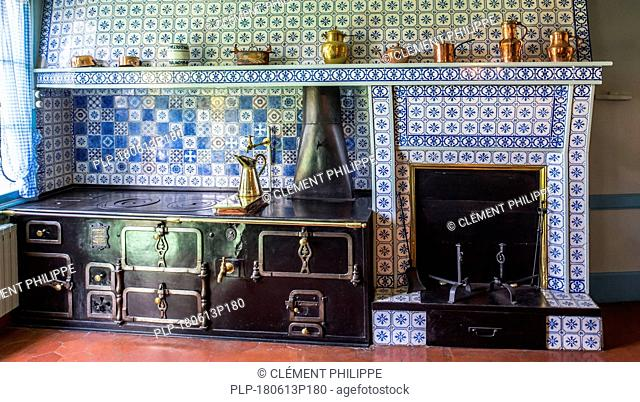Blue-tiled kitchen in the house of Claude Monet, painter and founder of French Impressionist painting at Giverny, Eure department, Normandy, France