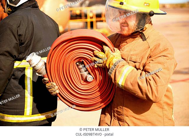 Fireman carrying fire hose reel, Darlington, UK