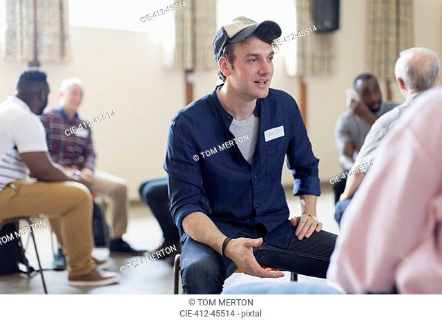 Young man talking in group therapy in community center
