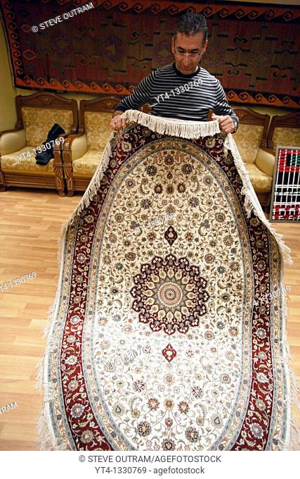 Mr Mehmet Polat displaying a hand made Silk Carpet from Konya Bosphorus Carpet Weavers Coop, Istanbul, Turkey