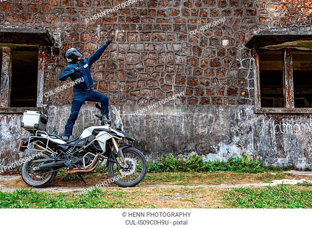 Biker posing in superhero gesture on ADV motorbike, Phnom Penh, Cambodia
