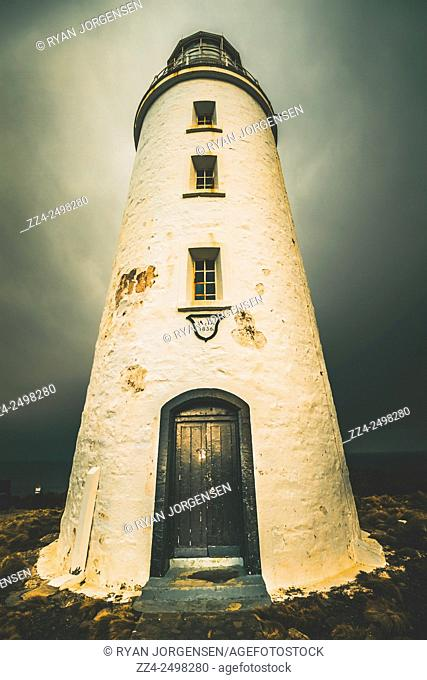 Dramatic and atmospheric vintage toned image of the second oldest extant lighthouse tower in Australia captured under stormy skies