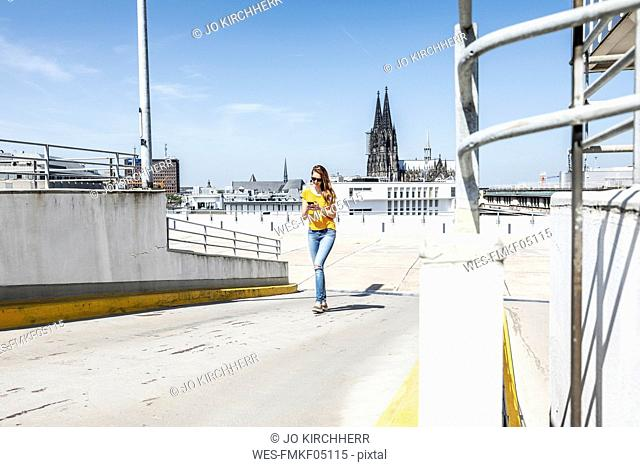 Germany, Cologne, woman walking on ramp of paking level using cell phone