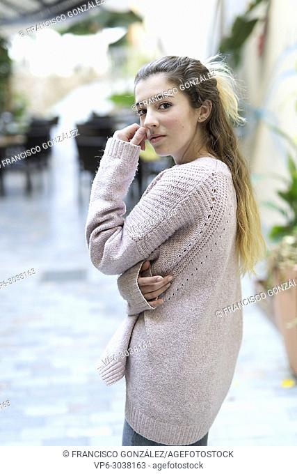 Young teenage girl with her hand on her face looking at the camera in the Spanish city of Orihuela