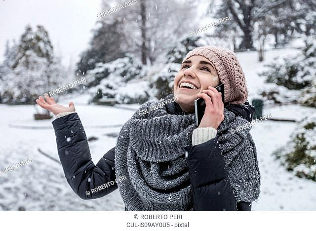 Woman on snow covered landscape using smartphone to make telephone call