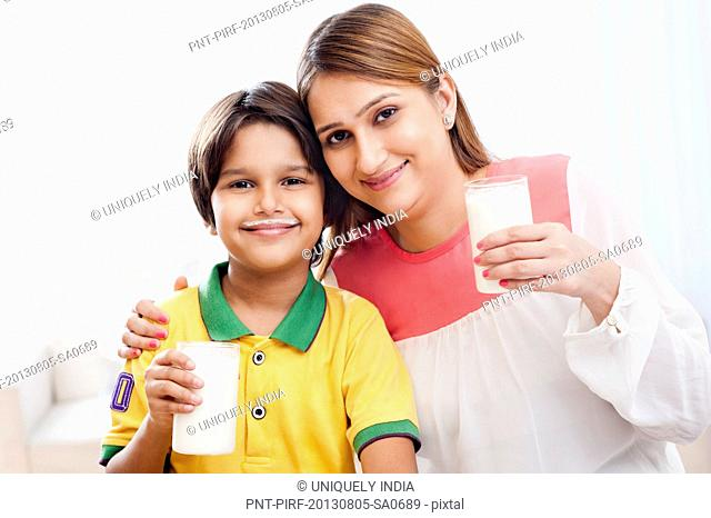 Portrait of a woman and her son holding glasses of milk