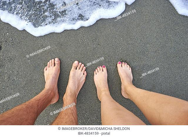 Two feet standing at the surf from the sea, Crete, Greece, Europe