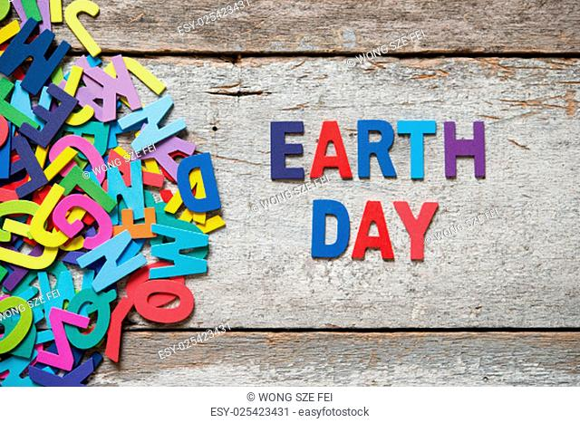 """The colorful words """"""""EARTH DAY"""""""" made with wooden letters next to a pile of other letters over old wooden board"""