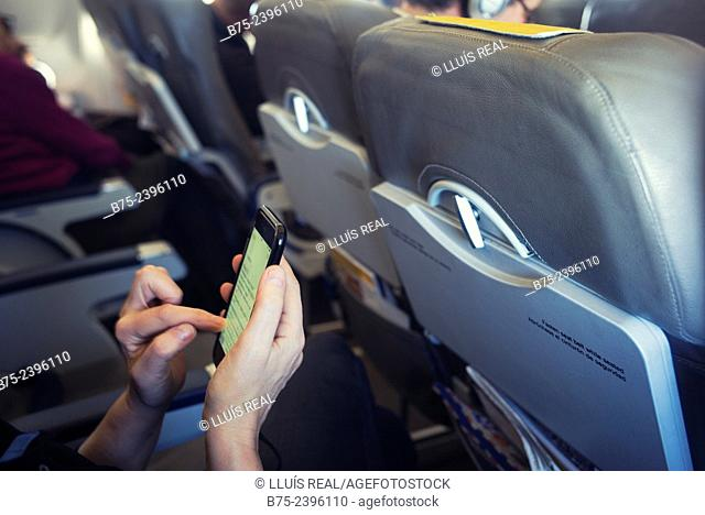 Closeup of hands of a young woman manipulating a mobile phone on an airplane