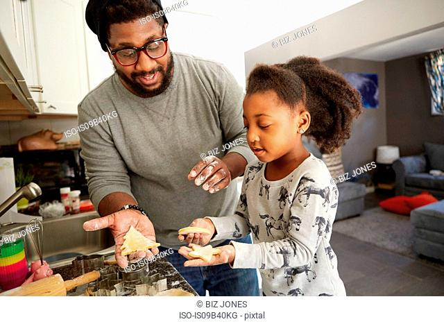 Father and daughter cutting cookies from cookie dough