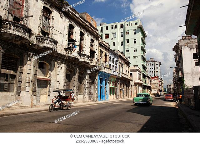 American cars and a bici-taxi on the road near Vedado, Havana, Cuba, West Indies, Central America